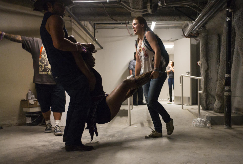 <p>People assist a wounded woman at the Tropicana as police confirmed more than 20 people killed by the shooter. (AP) </p>