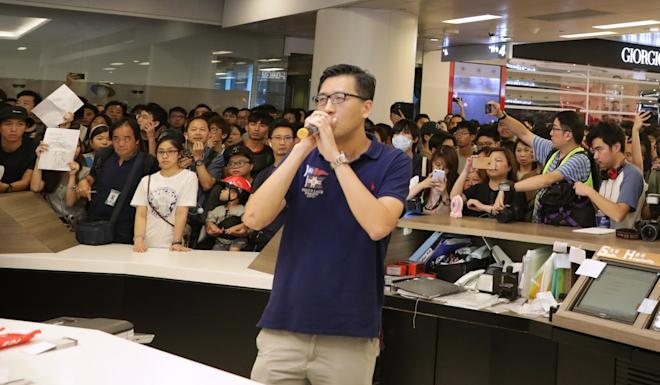 Democratic Party lawmaker Lam Cheuk-ting urges people to remain peaceful during the protest at New Town Plaza in Sha Tin on Tuesday. Photo: May Tse