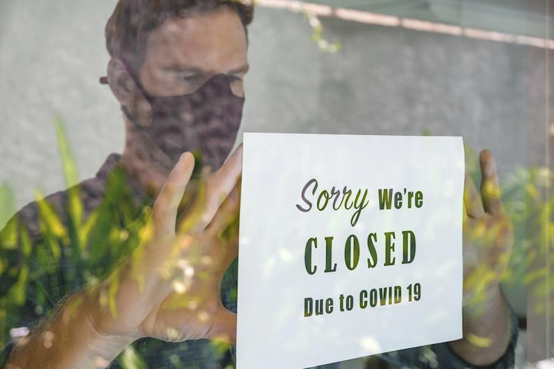 Portrait shot of business manputting a closing announcement message into the restaurant window due to Covid 19 pandemic