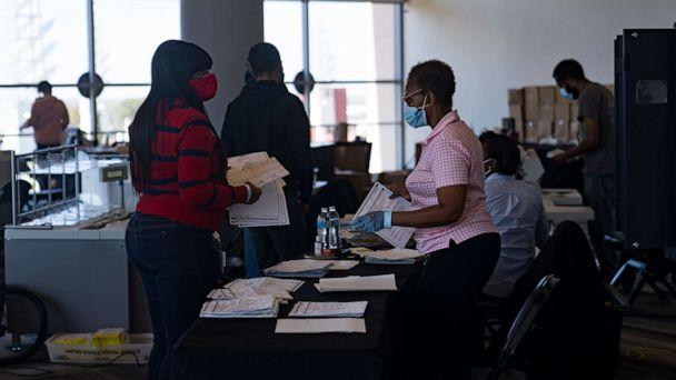 PHOTO: Two election workers talk while processing absentee ballots at State Farm Arena on Nov. 2, 2020, in Atlanta. (Megan Varner/Getty Images, FILE)