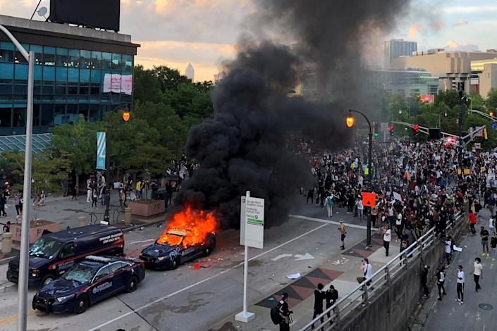 Picture: A police car in Atlanta burns as people protest near the CNN center in Atlanta (Dustin Chambers / Reuters)