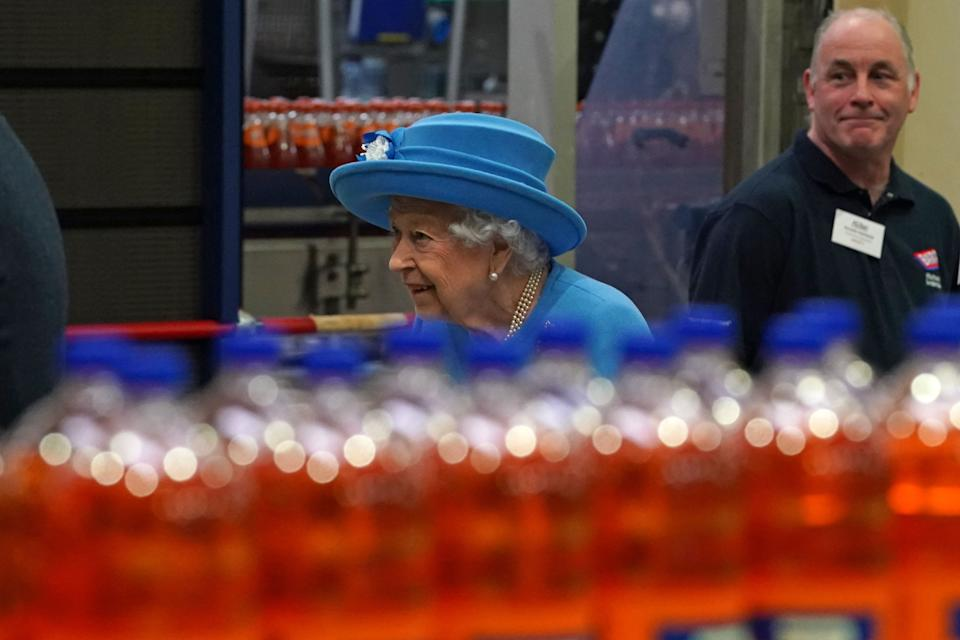 Britain's Queen Elizabeth II tours the production line during a visit to AG Barr's factory in Cumbernauld, east of Glasgow, where the Irn-Bru drink is manufactured on June 28, 2021. - The Queen is in Scotland for Royal Week where she will be undertaking a range of engagements celebrating community, innovation and history. (Photo by Andrew Milligan / POOL / AFP) (Photo by ANDREW MILLIGAN/POOL/AFP via Getty Images)