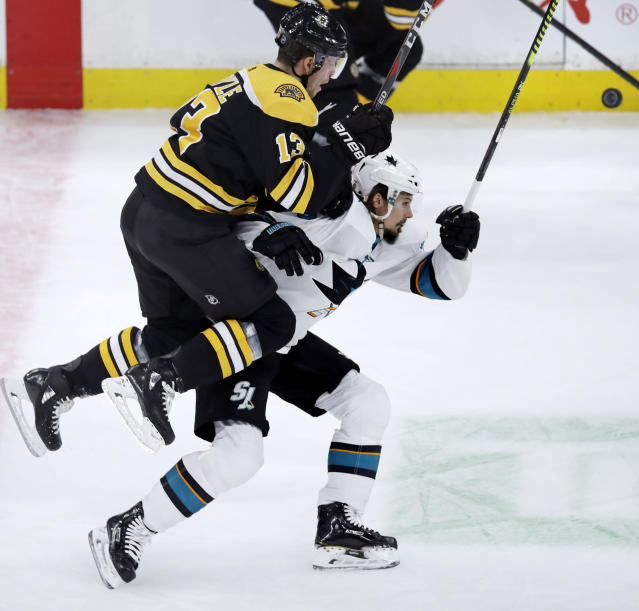 Boston Bruins center Charlie Coyle (13) leaps onto the back of San Jose Sharks defenseman Erik Karlsson, right, as they chase the puck during the first period of an NHL hockey game in Boston, Tuesday, Feb. 26, 2019. (AP Photo/Charles Krupa)
