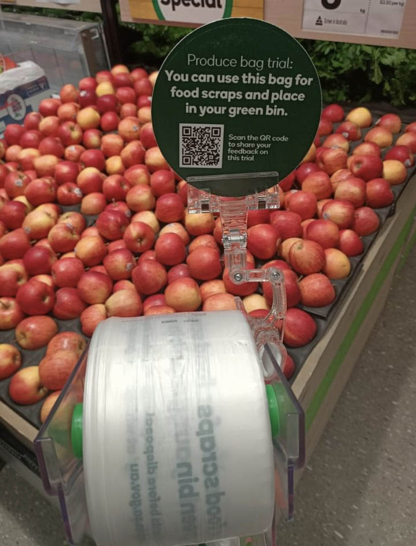Woolworths produce bags in front of an apple display. Source: Facebook