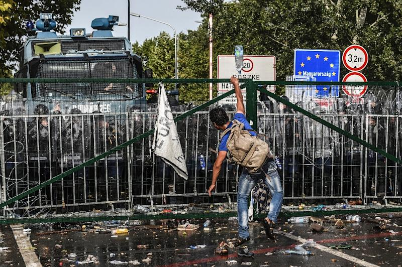 A refugee throws a bottle of water towards Hungarian riot police after they used water cannon to push back refugees at the Hungarian border with Serbia near the town of Horgos on September 16, 2015 (AFP Photo/Armend Nimani)