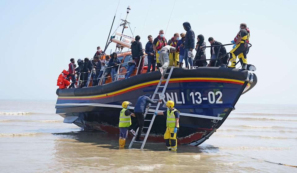 A group of people come ashore from the local lifeboat at Dungeness in Kent (Gareth Fuller/PA) (PA Wire)
