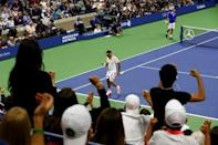 Fans celebrate after Roger Federer of Switzerland (in white) won a point against Novak Djokovic of Serbia in their men's singles final match at the U.S. Open Championships tennis tournament in New York, September 13, 2015. REUTERS/Lucas Jackson