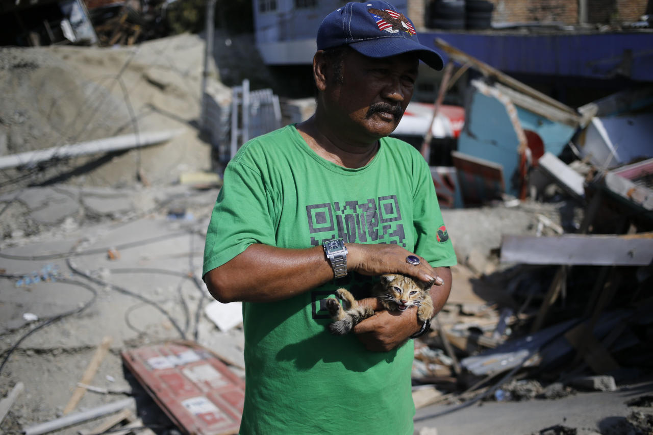 <p>Sa'adon Lawira holds his grandson's cat whose meow helped him finding his body, which was buried under the rubble of the family's house in the Balaroa neighborhood of Palu, Central Sulawesi, on 2 October. (PHOTO: Associated Press) </p>