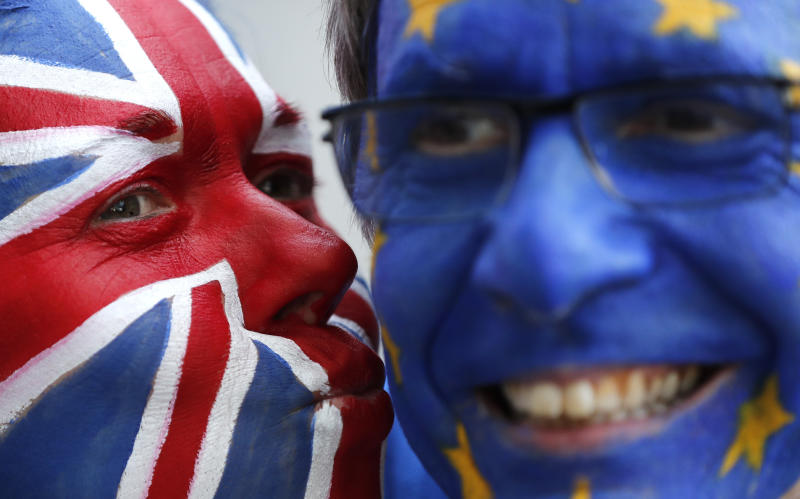 FILE - In this Thursday, March 21, 2019 file photo, activists pose with their faces painted in the EU and Union Flag colors during an anti-Brexit campaign stunt outside EU headquarters during an EU summit in Brussels. The country's struggle to leave the European Union is one of the great political crisis to afflict Britain in the postwar period. (AP Photo/Frank Augstein, File)