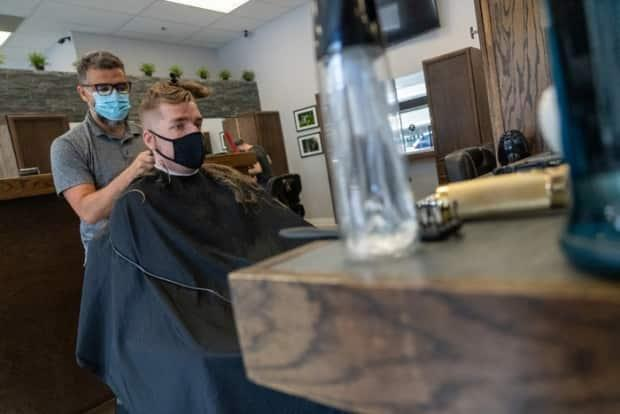 Bekkir Bouzioukh, left, cuts Gerard De Francesco's hair at the Hair Fellas barbershop on Slater Street in downtown Ottawa on June 30, 2021, during the COVID-19 pandemic. (Francis Ferland/CBC - image credit)