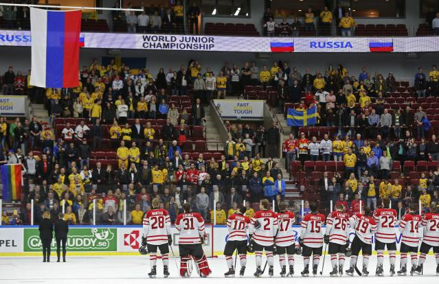 Members of Canada watch the Russian flag being raised after Russia won the bronze medal following their IIHF World Junior Championship ice hockey game in Malmo, Sweden, January 5, 2014. REUTERS/Alexander Demianchuk (SWEDEN - Tags: SPORT ICE HOCKEY)