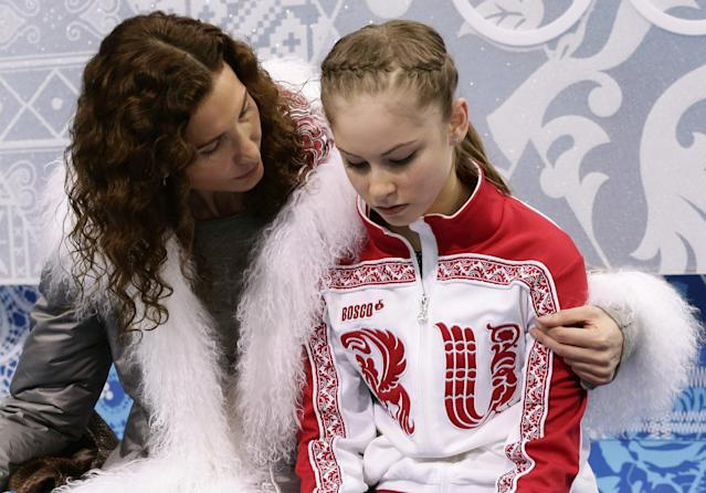Julia Lipnitskaya of Russia, right, and her coach Eteri Tutberidze wait in the results area after she completed her routine in the women's short program figure skating competition at the Iceberg Skating Palace during the 2014 Winter Olympics, Wednesday, Feb. 19, 2014, in Sochi, Russia. (AP Photo/Bernat Armangue)