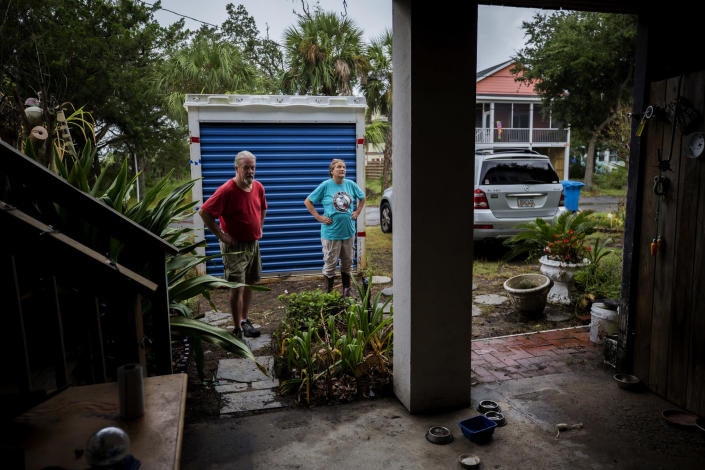 Sandy Cason, center, and her husband David Cason, left, stand outside their home before evacuating as Hurricane Dorian makes its way up the east coast, Wednesday, Sept. 4, 2019, in Tybee Island, Ga. The Casons are still repairing damage from the two previous storms that came close to the coastal barrier island. Sandy Cason said she's not ready to blame climate change. She noted records show Georgia got hit by several powerful hurricanes in the 1800s. (AP Photo/Stephen B. Morton)
