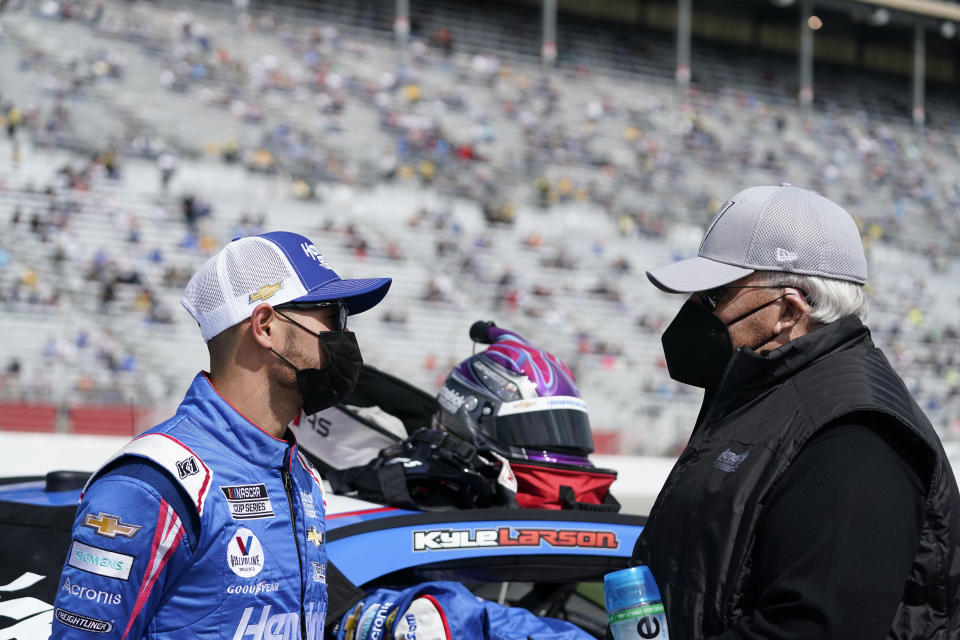 NASCAR Cup Series driver Kyle Larson, left, talks to the owner of the NASCAR team Hendrick Motorsports, Rick Hendrick, right, before a NASCAR Cup Series at Atlanta Motor Speedway on Sunday, March 21, 2021, in Hampton, Ga. (AP Photo/Brynn Anderson)