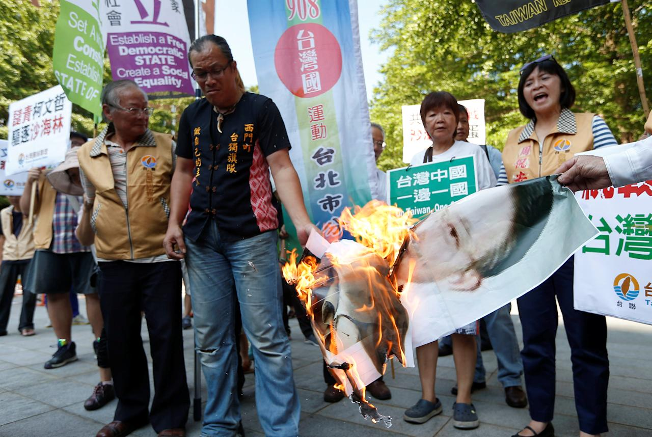 Anti-China protesters burn a photo of Sha Hailin, a member of Shanghai's Communist Party standing committee and head of the United Front Work Department, before the opening ceremony of Taipei-Shanghai forum, in Taipei, Taiwan August 23, 2016. REUTERS/Tyrone Siu