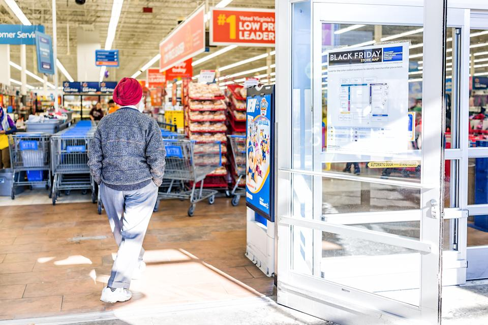 Burke, USA - November 24, 2017: Black Friday sign in Walmart store entrance with map after Thanksgiving shopping consumerism in Virginia with sikh man walking inside