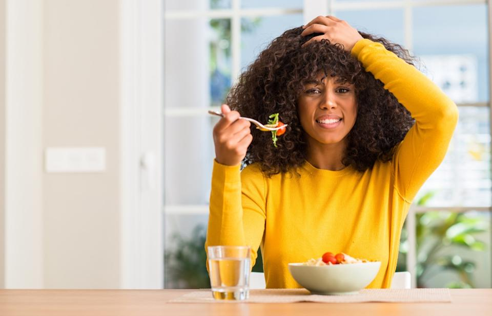 African american woman eating pasta salad at home stressed with hand on head, shocked with shame and surprise face, angry and frustrated. Fear and upset for mistake.