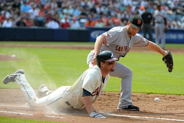 Atlanta Braves' Chris Johnson, bottom, is safe at first on an infield grounder as San Francisco Giants pitcher Chad Gaudin fields the late throw during the second inning of their baseball game at Turner Field, Saturday, June 15, 2013, in Atlanta. (AP Photo/David Tulis)