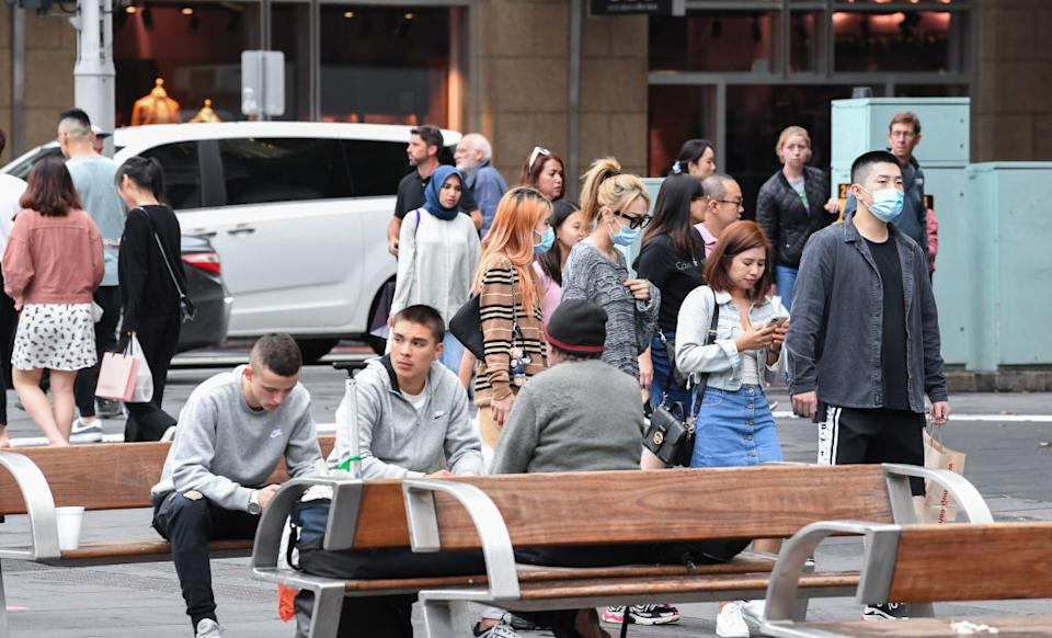 A group of people sit on a bench at Sydney's Town Hall as some walk past with face masks.