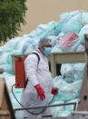 A medical worker using protective equipment disinfects a large pile of hazardous biological waste outside the Hospital del Instituto Mexicano del Seguro Social, which treats patients with COVID-19 in Veracruz, Mexico, Wednesday, Aug. 12, 2020. Improper disposal of medical waste has become an increasing problem in Mexico amid the pandemic. (AP Photo/Felix Marquez)