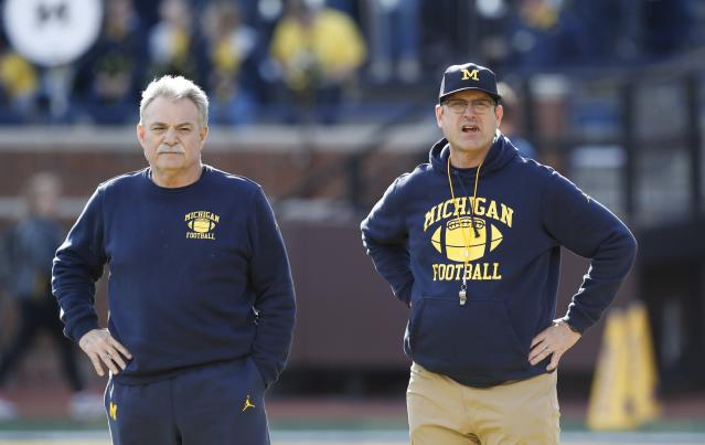 Michigan defensive coordinator Don Brown, left, and head coach Jim Harbaugh watch the team's annual spring NCAA college football game, Saturday, April 13, 2019, in Ann Arbor, Mich. (AP Photo/Carlos Osorio)