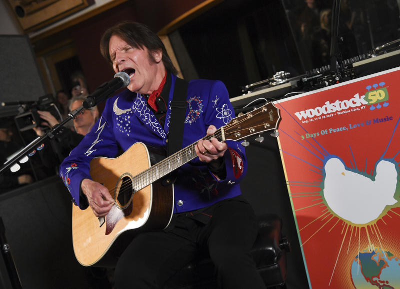 FILE - In this March 19, 2019, file photo, musician John Fogerty performs at the Woodstock 50 lineup announcement at Electric Lady Studios in New York. Fogerty has pulled out of Woodstock 50 weeks before the trouble anniversary event is supposed to take place. A representative for the singer tells The Associated Press that Fogerty, who performed at the original festival in 1969, will now only perform at a smaller Woodstock anniversary event held at the original site in Bethel, New York. (Photo by Evan Agostini/Invision/AP, File)