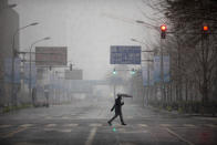 A man wears a mask as he walks across an empty intersection during the morning rush hour as snow falls in Beijing, Friday, Feb. 14, 2020. China on Friday reported another sharp rise in the number of people infected with a new virus, as the death toll neared 1,400. (AP Photo/Mark Schiefelbein)