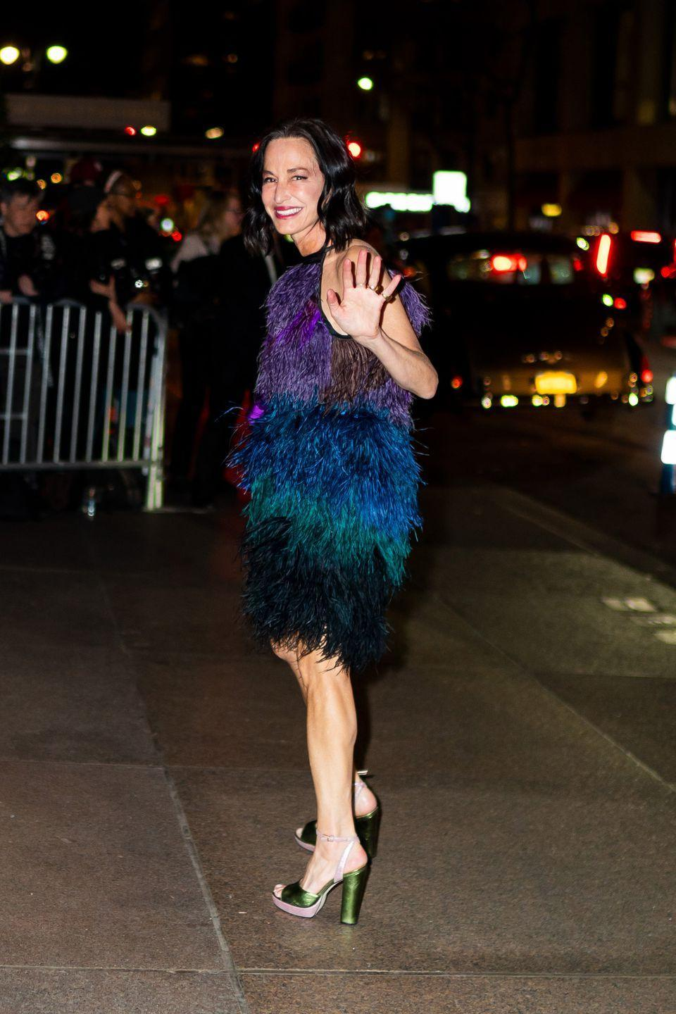 <p>The designer wore a multi-colored dress and chunky platform heels.</p>