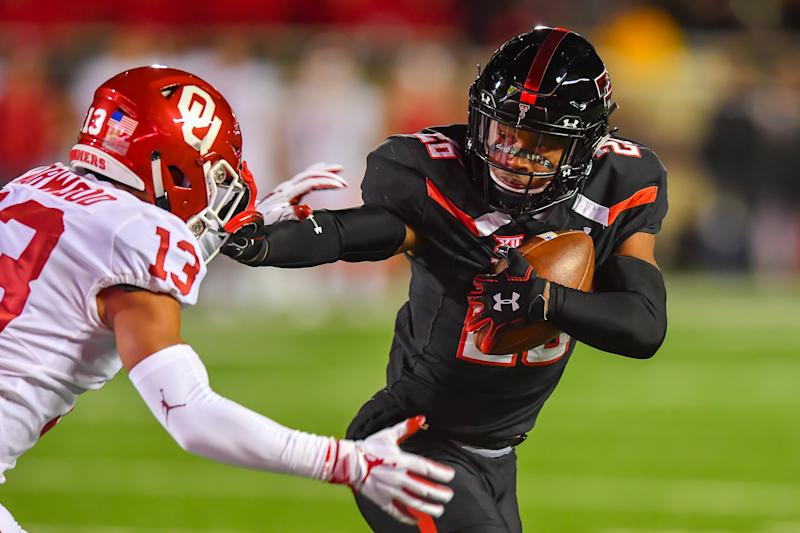 LUBBOCK, TX - NOVEMBER 03: Ta'Zhawn Henry #26 of the Texas Tech Red Raiders gets past Tre Norwood #13 of the Oklahoma Sooners during the first half of the game on November 3, 2018 at Jones AT&T Stadium in Lubbock, Texas. (Photo by John Weast/Getty Images)