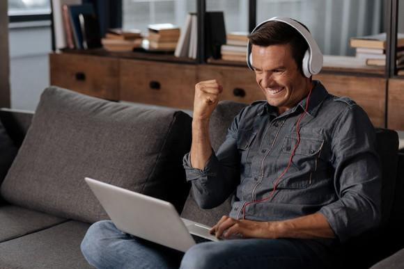 A man wearing headphones cheers as he looks at his laptop.