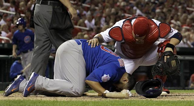 St. Louis Cardinals catcher Yadier Molina, top, checks on Chicago Cubs' Dioner Navarro after Navarro was hit by a pitch during the sixth inning of a baseball game Friday, Sept. 27, 2013, in St. Louis. Navarro was able to stay in the game. (AP Photo/Jeff Roberson)