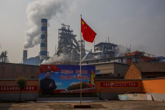 A poster showing Chinese President Xi Jinping is seen in front of the Xinyuan Steel plant in Anyang (Reuters)