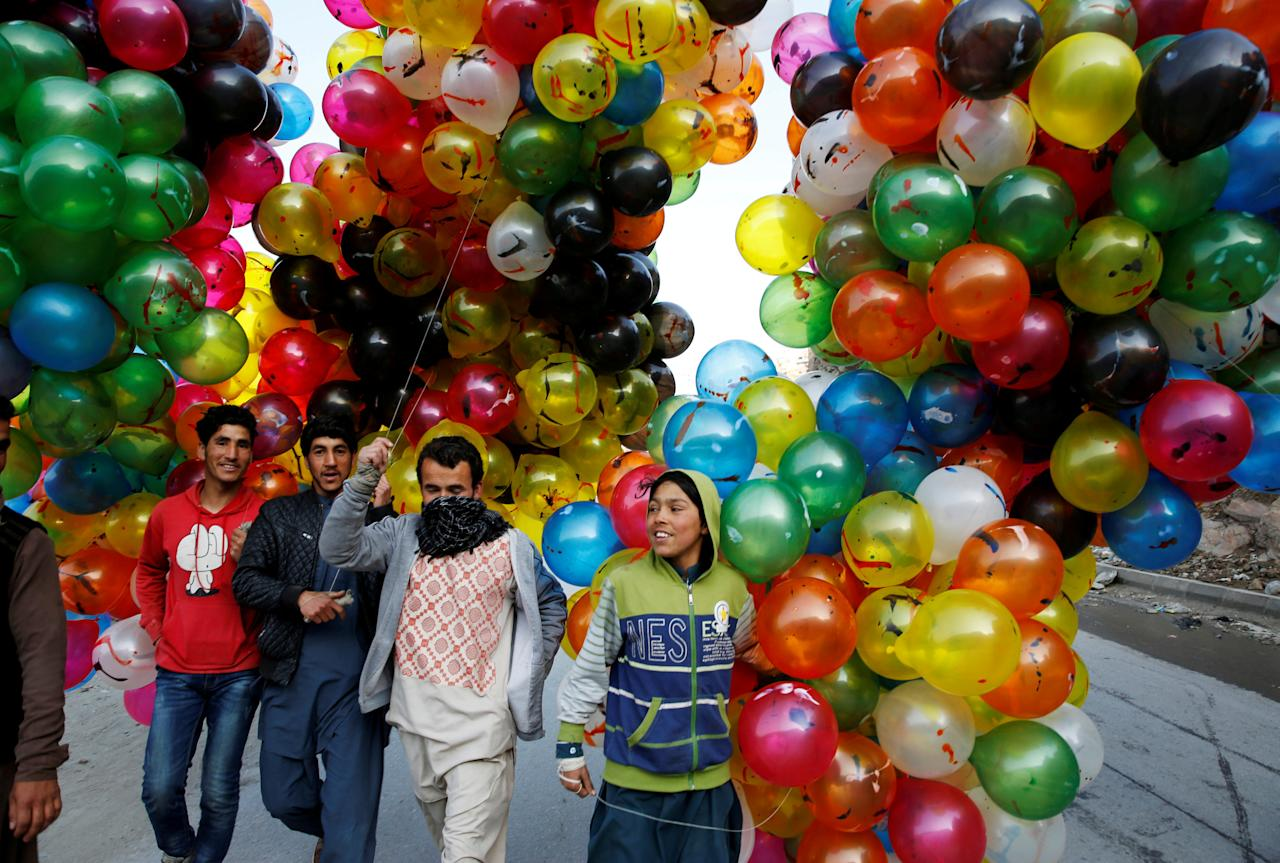 Men hold balloons for sale during Afghan spring and new year celebrations in Kabul, Afghanistan March 21, 2018. REUTERS/Mohammad Ismail     TPX IMAGES OF THE DAY
