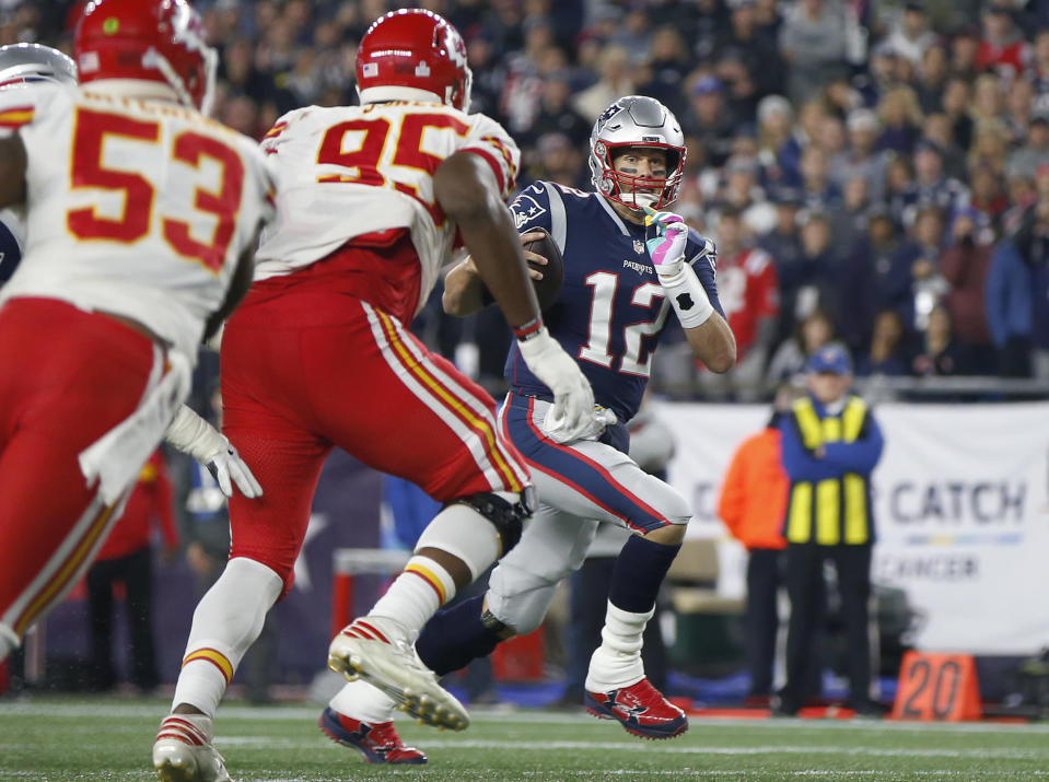 New England Patriots quarterback Tom Brady (12) runs past Kansas City Chiefs linebacker Anthony Hitchens (53) and defensive tackle Chris Jones (95) for a touchdown during the second half of an NFL football game, Sunday, Oct. 14, 2018, in Foxborough, Mass. (AP Photo/Michael Dwyer)