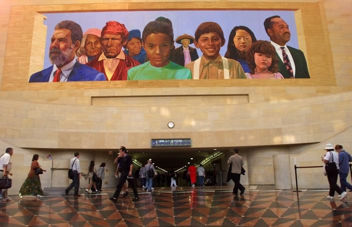 """FILE - In this Aug. 30, 2000, file photo, commuters walk into a tunnel at Los Angeles's Amtrack-Metrolink Union Station under the mural """"City of Dreams/River of History"""" by artist Richard Wyatt, showing the diversity of California's population. Many U.S. companies have rushed to appoint Black members to their board of directors since racial justice protests swept the country last year. But in the two preceding years, progress on increasing racial diversity on boards stagnated, a new study revealed Tuesday, June 8, 2021. California Gov. Gavin Newsom signed a new law last year giving companies until the end of 2021 to have at least one board member from an underrepresented ethnic communities, or who identify as LBGT. (AP Photo/Damian Dovarganes, File)"""