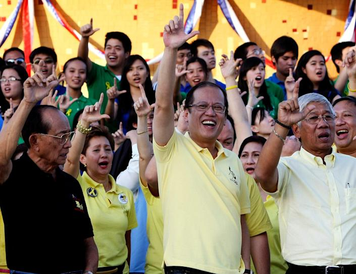 Aquino flashes the 'L' sign (for 'laban', or 'fight') on the 25th anniversary of the 1986 revolution - Bullit Marquez/AP