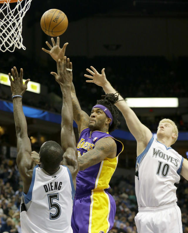 Los Angeles Lakers forward Jordan Hill, center, shoots over Minnesota Timberwolves center Gorgui Dieng (5) and forward Chase Budinger (10) during the second quarter of an NBA basketball game in Minneapolis, Friday, March 28, 2014. (AP Photo/Ann Heisenfelt)