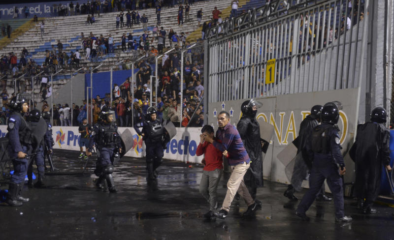 A man and youth walk with their eyes shut due to tear gas fired by police trying to break up a deadly fight between fans before the start of a game between Motagua and Olimpia, inside the national stadium in Tegucigalpa, Honduras, late Saturday, Aug. 17, 2019. The fight between fans of rival soccer teams outside the stadium left three people dead and led to the suspension of the game. (Victor Colindres/La Tribunal via AP)
