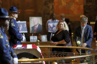 Visitors place flowers as former Louisiana Governor Edwin W. Edwards lies in state in Memorial Hall of the Louisiana State Capitol in Baton Rouge, La., Saturday, July 17, 2021. The colorful and controversial four-term governor died of a respiratory illness on Monday, July 12. (AP Photo/Michael DeMocker)