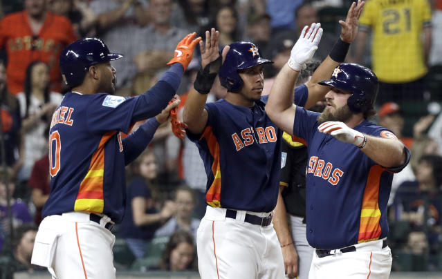 Houston Astros' Tyler White, right, celebrates with Michael Brantley, center, and Yuli Gurriel, left, after they scored on White's home run against the Pittsburgh Pirates during the third inning of an exhibition baseball game Monday, March 25, 2019, in Houston. (AP Photo/David J. Phillip)