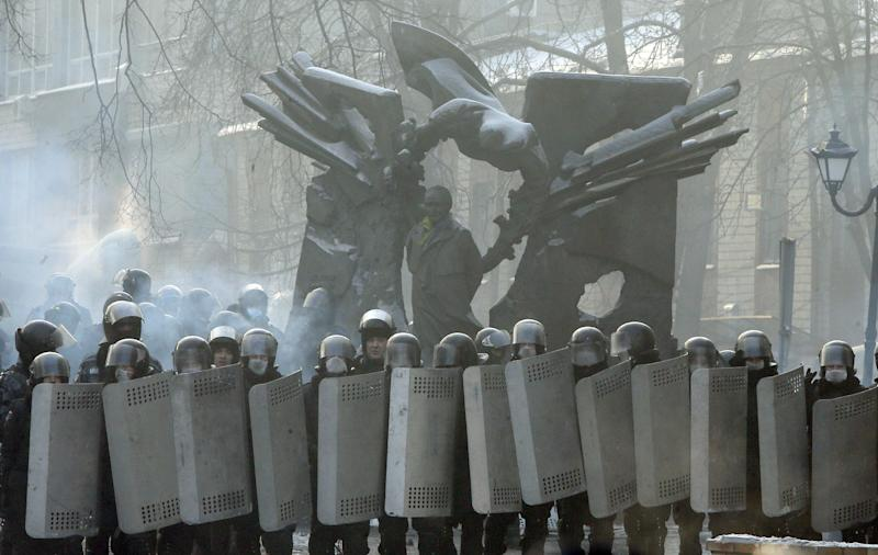 Riot police officers block a street in front of barricades of protesters at the monument to Viacheslav Chornovil, a prominent politician in Ukraine and a former Soviet political prisoner, in central Kiev, Ukraine, Friday, Jan. 24, 2014. Protesters have seized a government building in the Ukrainian capital while also maintaining the siege of several governors' offices in the country's west, raising the pressure on the government. After meeting with President Viktor Yanukovych on Thursday, opposition leaders told the crowds that he has promised to ensure the release of dozens of protesters detained after clashes with police and stop further detentions. (AP Photo/Efrem Lukatsky)
