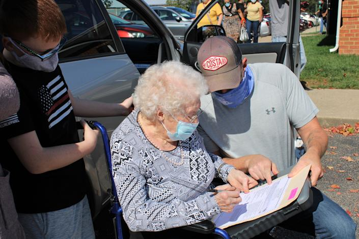 Centenarian Mabel Dorothy Duty Cook of Chesterfield with her grandson Curtis Litton's assistance fills out her ballot while her great-grandson Jack Litton looks on at the Registrar's Office in Chesterfield on Oct. 15, 2020.
