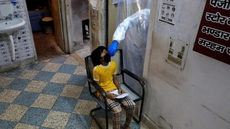 A health worker in personal protective equipment collects a sample using a swab from a girl at a health centre to conduct tests in Delhi, 27 June