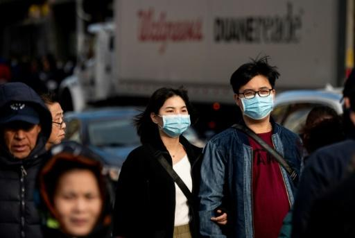 People wear face masks as they walk down a street in Flushing area of Queens on March 2, 2020 in New York City