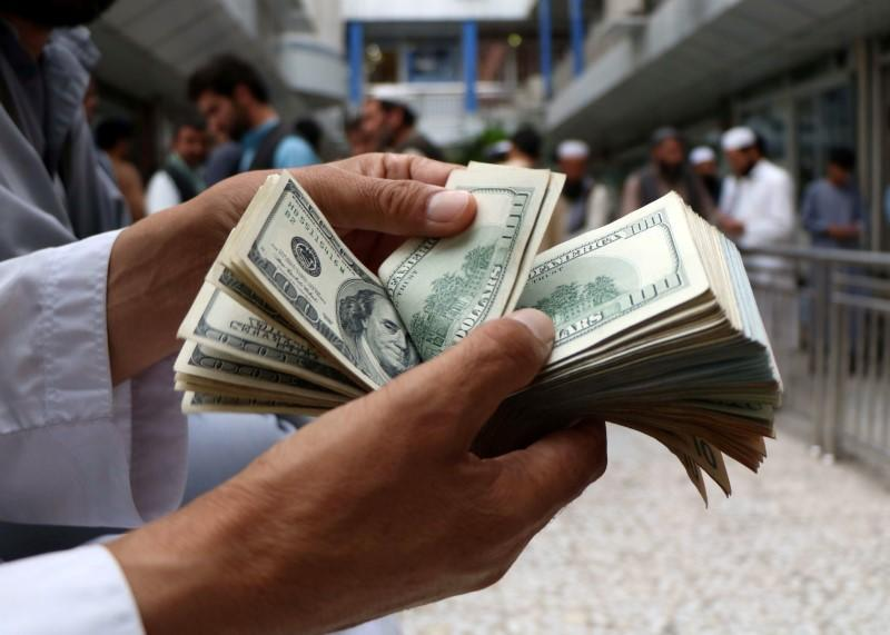 A money changer counts U.S. dollar banknotes at money change market in Herat province