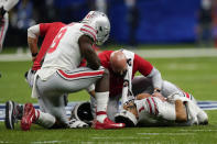 Ohio State quarterback Justin Fields is treated on the field after getting hit by Clemson linebacker James Skalski during the first half of the Sugar Bowl NCAA college football game Friday, Jan. 1, 2021, in New Orleans. Skalski was ejected from the game for targeting. (AP Photo/Gerald Herbert)