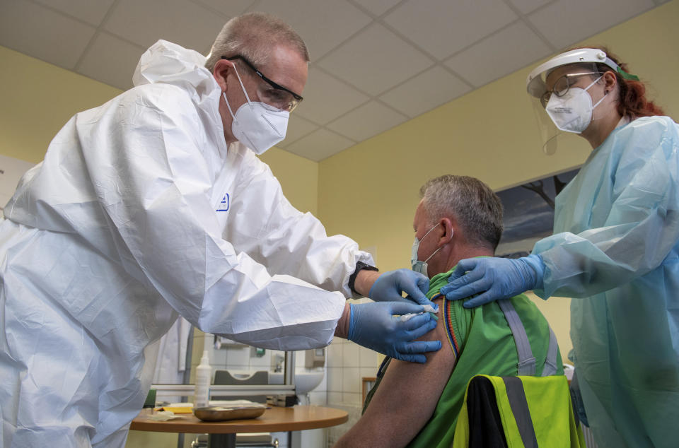 Harry Hoffmann, left, a Volkswagen company doctor, and nurse Nicolle Sprotte, right, vaccinate Steffen Martin, an employee at the Volkswagen Saxony plant, with the AstraZeneca vaccination in Zwickau, Germany, Tuesday, March 30, 2021. (Hendrik Schmidt/dpa via AP)