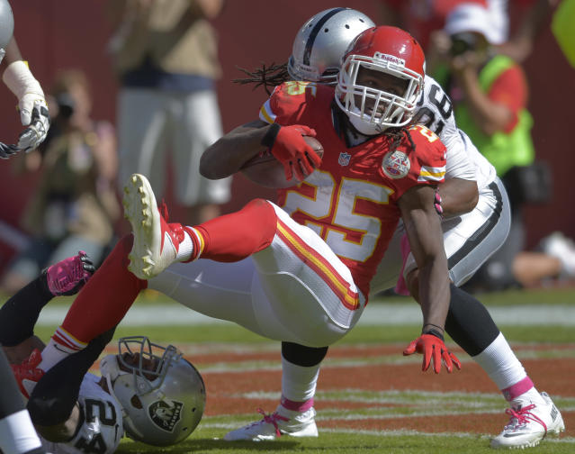 Kansas City Chiefs running back Jamaal Charles (25) crosses the goal line for a touchdown as Oakland Raiders free safety Usama Young (26) defends during the first half of an NFL football game at Arrowhead Stadium in Kansas City, Mo., Sunday, Oct. 13, 2013. (AP Photo/Reed Hoffmann)