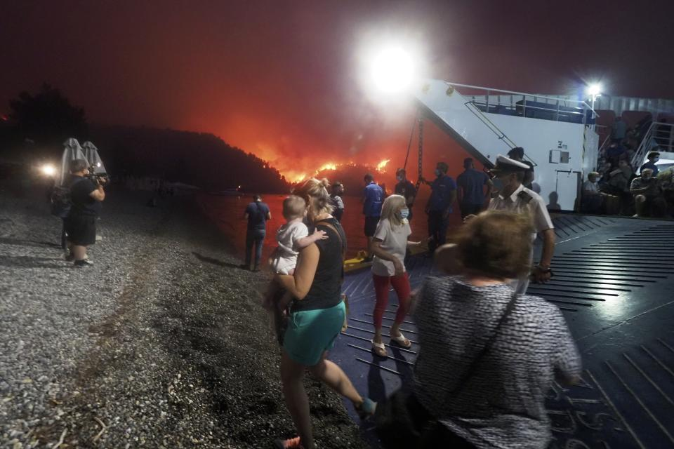 A woman carries a baby as people evacuate from Evia during a wildfire.