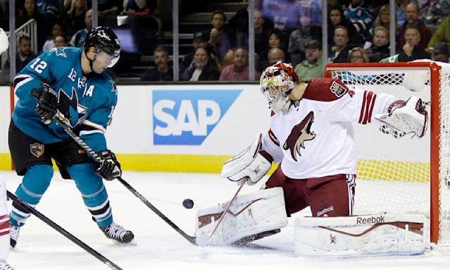 Phoenix Coyotes goalie Mike Smith, right, deflects a shot next to San Jose Sharks center Patrick Marleau (12) during the first period of an NHL hockey game on Saturday, Nov. 2, 2013, in San Jose, Calif. (AP Photo/Marcio Jose Sanchez)